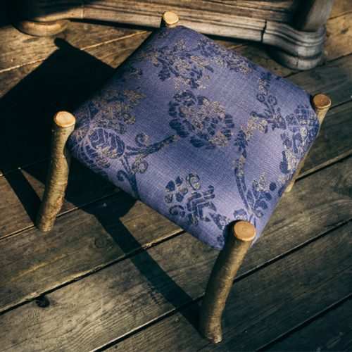 Handmade wooden footstool. Coppiced hazel wood frame upholstered in Purple and Gold fabric