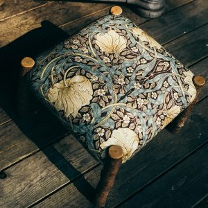This is a hand crafted Birch Wood footstool upholstered in Morris & Co Pimpernel fabric. There is a sense of movement in the fabric as the large flowers curl in circles with the leaves flowing like ribbons on this Arts and Crafts designer print footstool.