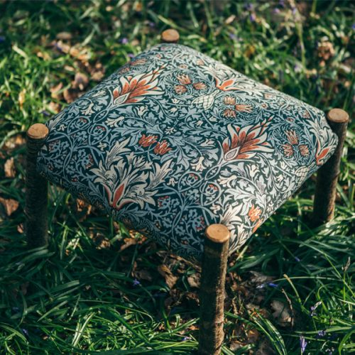 Hand made unique wooden footstool. The stool is upholstered in Arts and Crafts Designer William Morris Print. The classic Morris and Co print features repeated symmetrical patterns and nature motifs.